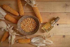 óleo de milho e grãos de milho em fundo de madeira de padrão natural foto