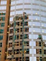 fachada de um edifício moderno de vidro com reflexos do céu azul foto