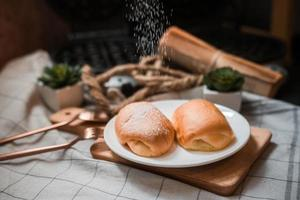 Pão de manteiga macio com açúcar de confeiteiro em um prato de madeira foto