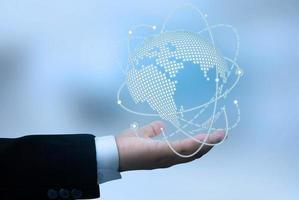 mão do empresário segurando a conexão de rede global e o globo da terra com pontos e linhas. foto