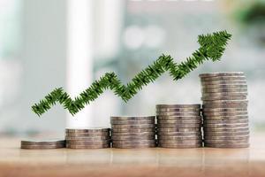 conceito de crescimento de negócios e finanças. gráfico de crescimento de folha verde na pilha de moedas de prata. foto