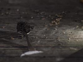 folhas secas de chá preto na colher de metal foto