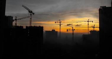 construção de edifícios com guindastes durante o pôr do sol foto