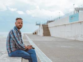 homem barbudo com moicano sentado em um banco de concreto foto