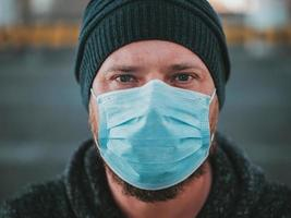 Feche o retrato de um homem moderno com uma máscara médica foto