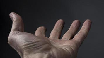 a mão do homem implora por algo em um fundo escuro foto