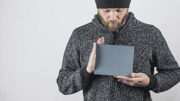 homem barbudo segura nas mãos uma placa de papelão cinza em branco foto