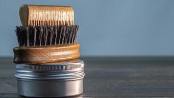 escova de barba, pente de madeira para barba e frasco de cera foto