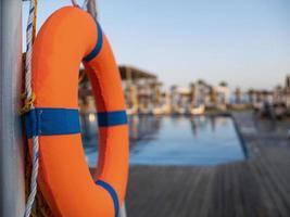 bóia salva-vidas laranja perto de uma piscina pública em um fundo desfocado, uma piscina é visível foto