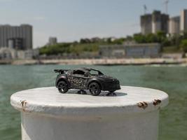 modelo de carro de brinquedo em preto contra o fundo do mar e edifícios altos foto