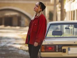 Uma bela jovem loira hippie está perto de um carro velho na rua foto