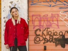 uma jovem com um chapéu de malha e uma jaqueta vermelha está encostada na parede pintada de uma garagem foto