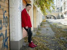 linda garota com uma jaqueta vermelha de chapéu de malha e botas vermelhas em pé perto de uma parede em pleno crescimento ao ar livre foto