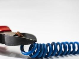 close-up de um alicate vermelho e fio trançado azul no fundo branco. Alicate de corte de cabo foto