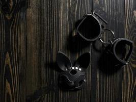 algemas de couro e uma máscara de coelho em uma mesa de madeira. brinquedos para adultos. fetiche. vista superior do kit de couro bdsm foto