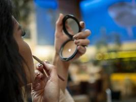 linda garota se olha em um pequeno espelho e pinta os lábios com um delineador de lábios foto