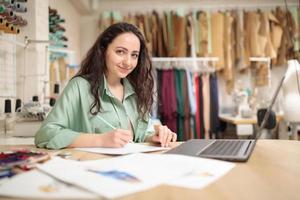 elegante designer feminino trabalhando no laptop e desenhando na mesa em estúdio. trabalhador da moda jovem na oficina foto