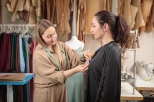 modelo de moda ajustando roupas por um estúdio de designer profissional, tomando medidas foto