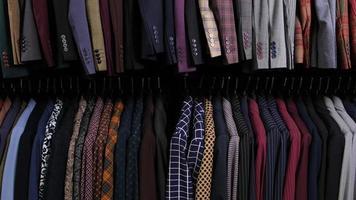 moda masculina ternos diferentes clássicos em cabides em linha na loja de roupas no shopping. muitas fantasias em prateleiras na loja. conceito de negócio e varejo. vista de uma linha de mangas de jaquetas com botões. foto
