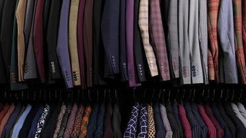 moda masculina ternos diferentes clássicos em cabides em linha na loja de roupas no shopping. muitas fantasias em prateleiras na loja. conceito de negócio e varejo. foto