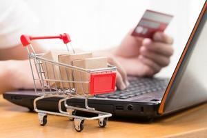mão homens usando laptop e comprar produtos de um vendedor na Internet. conceito de compras online foto