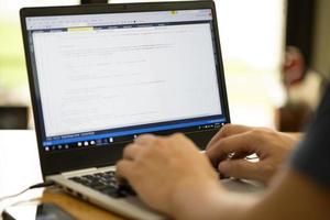 programador ou desenvolvedor freelance trabalhando em casa e digitando o código-fonte com um laptop foto