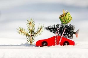 carrinho de brinquedo de madeira vermelho com árvore de natal e caixa de presente de natal foto