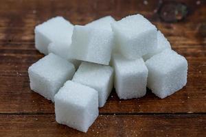 cubos de açúcar em fundo rústico de madeira foto