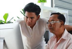 filho ensina pai a usar computador foto