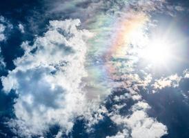 céu azul nuvens brancas sol e arco-íris foto