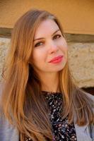 garota sorrindo com aparelho, atendimento odontológico e alegre, cabelos loiros compridos. Mulher sentada em um café com um sorriso mostrando os dentes foto