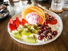 deliciosos crepes caseiros saborosos com sorvete de morango, crepes recheados com morangos, kiwi, uva foto