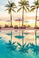 guarda-chuva e cadeira ao redor da piscina em hotel resort com nascer do sol pela manhã foto