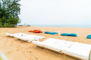 cadeira de praia vazia na areia com fundo do mar oceano foto