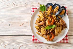 macarrão espiral frito com frutos do mar e molho de manjericão - estilo de comida de fusão foto
