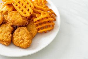 nuggets de frango frito com batatas fritas no prato foto