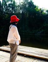 vista traseira de uma mulher solitária vestida de vermelho sentada no chão de bambu, olhando para a floresta verde e o rio foto