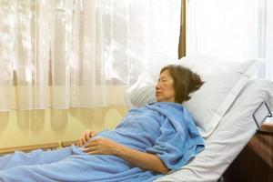 mulher asiática sênior deitada na cama ao lado da janela por causa da gripe foto
