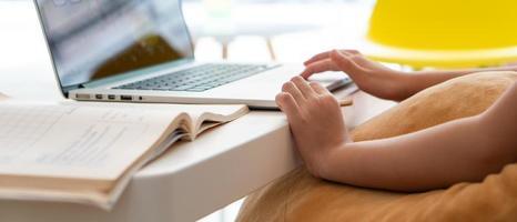 uma jovem asiática usando o computador para leran em casa como protocolo de distanciamento social durante covid-19 ou pandemia de coronavírus. conceito de ensino em casa foto