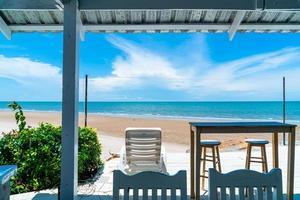 bar e cadeira de madeira com oceano, praia e céu azul foto
