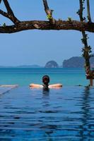 retrato de uma jovem de biquíni em pé na piscina azul infinita, olhando para a vista de Oceania nas férias de verão foto