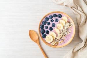 tigela de iogurte ou smoothie com mirtilo, banana e granola - estilo de comida saudável foto