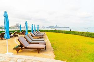 Piscina com cadeiras ou piscina com cama e guarda-sol ao redor da piscina com fundo de praia do mar em Pattaya, na Tailândia foto
