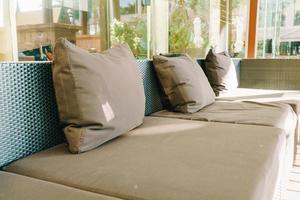 decoração de travesseiro confortável no sofá na área da varanda foto