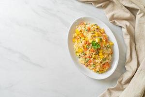 arroz frito caseiro com vegetais mistos de cenoura, feijão verde, milho e ovo foto