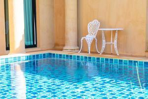 cadeira branca vazia e mesa ao lado da piscina foto