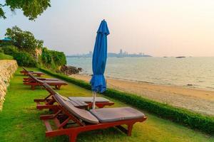 cadeiras de praia com o fundo do mar na hora do pôr do sol em Pattaya, Tailândia foto