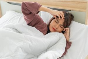mulher asiática com dor de cabeça e dormindo na cama foto