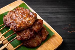 Carne de porco grelhado no espeto com arroz branco pegajoso - comida de rua tailandesa local foto