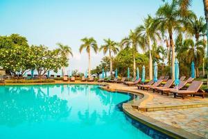 espreguiçadeiras e guarda-sóis ao redor da piscina com coqueiros - feriados e conceito de férias foto